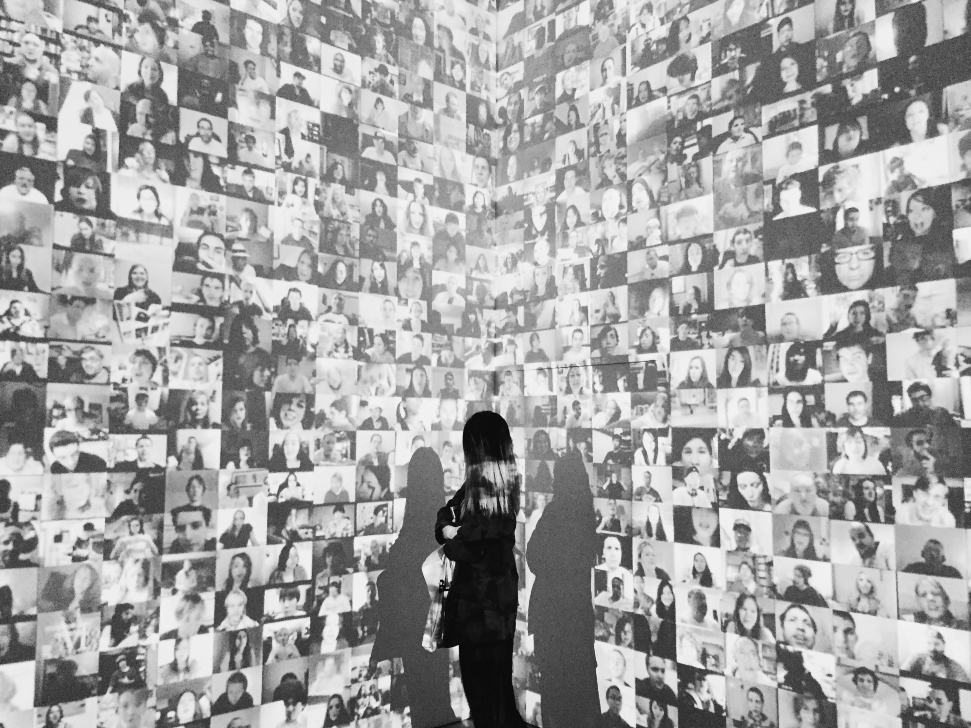 Young woman looking a wall of snapshots