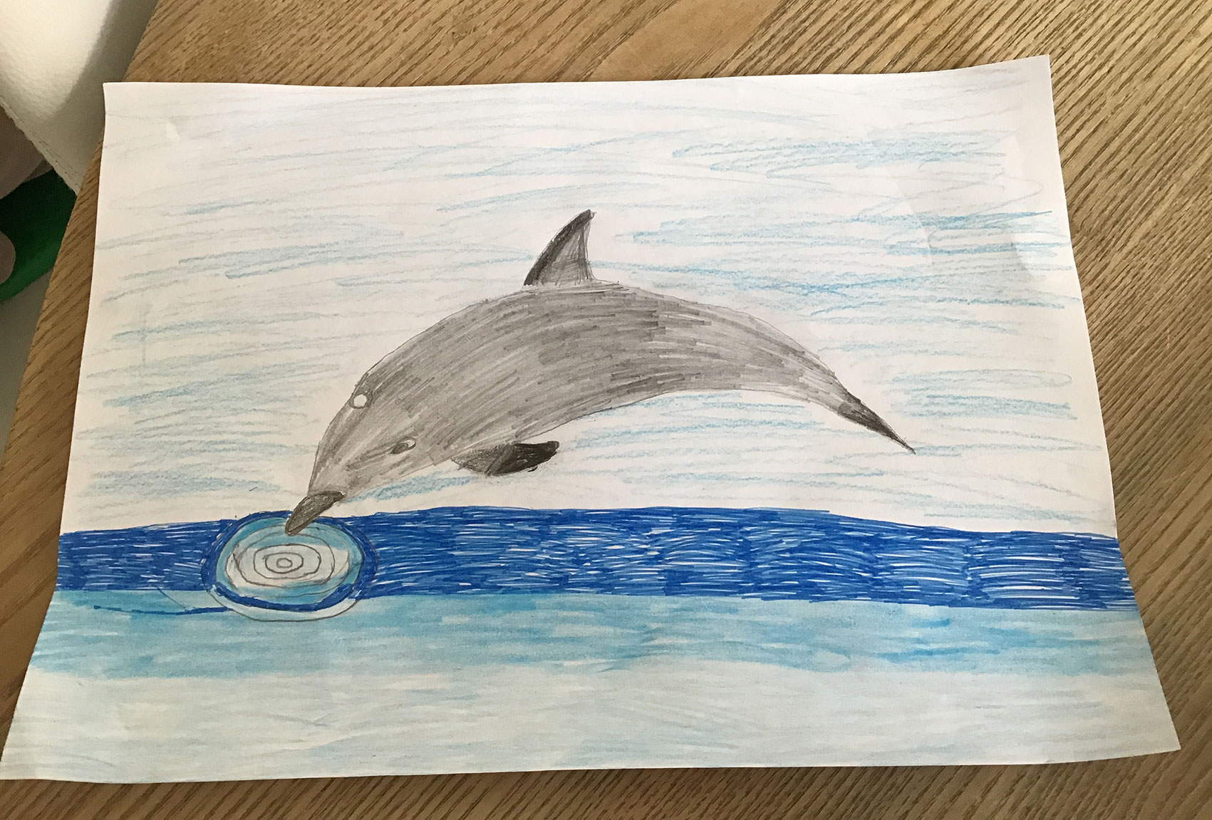 Child's drawing of a dolphin diving into the sea